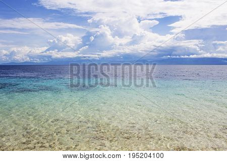 Seaside landscape with turquoise water and tropical island. Sea view with distant island. White fluffy clouds above blue ocean. Sea and sky minimal photo background. Idyllic seashore with white sand
