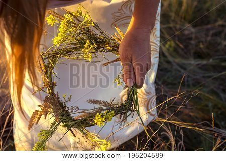 A Girl In White Traditional Slavic Dress Wreathes A Wreath Of Fresh Wildflowers At Sunset. Russian T