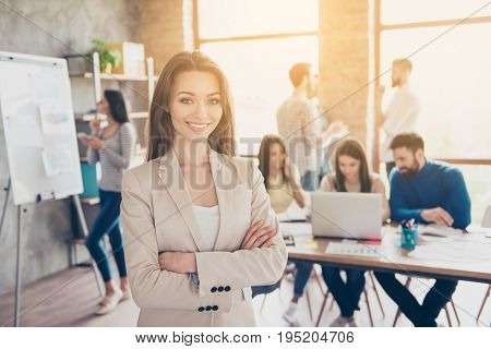 One for all and all for one. Success concept. Cheerful young lady is with partners in modern light office smiling standing in formal wear