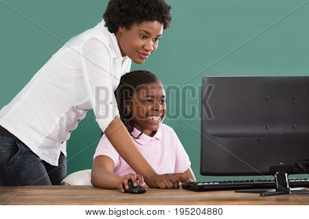 Teacher And Student Looking At Computer In Classroom Against Green Chalkboard