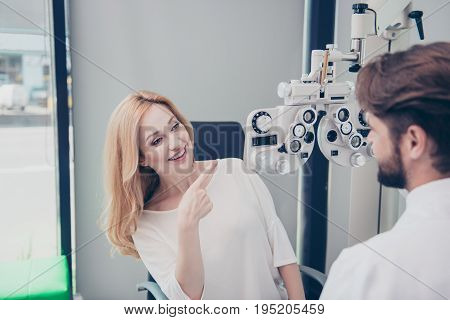 Optometrist Consultation. Blond Lady Patient Is Asking Brunet Bearded Male Doctor Optician About The