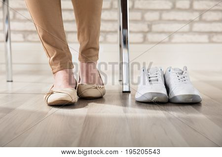 Pair Of A White Sport Shoes Besides Businesswoman's Legs In Office