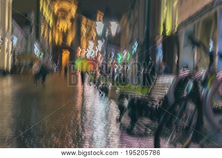 Abstract blurred background of girl under colorful vivid umbrella in city street in rain. Light illumination from lanterns and shop windows. Impressionism style. Intentional motion blur. Concept of seasons, weather, modern city, lifestyle, leisure.