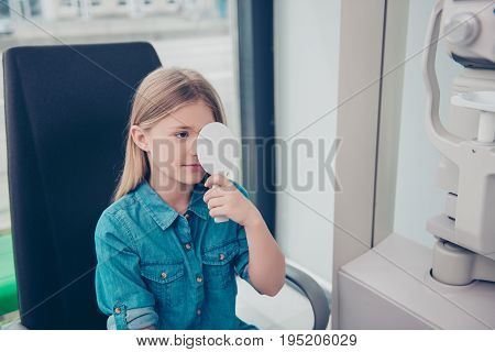 Nice little blond girl in jeans casual outfit at the ophthalmologist on consultation is covering her eye for checking her visual acuity