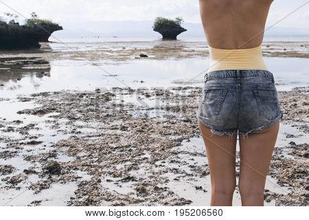 Woman in boho shorts and swimsuit on beach. Seashore and mountains on low tide. Summer travel trendy toned photo. Seaside hipster banner template. Summer holiday social media background. Girl vacation