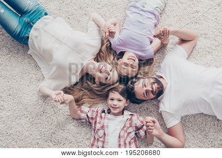 Top View Of Four Relatives, Lying On The Beige Cozy Carpet At Home, Holding Hands, All Smiling, Wear