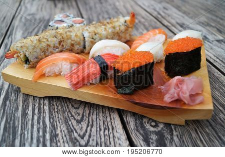 Sushi on wood table. Authentic sushi scene featuring a light wood serving tray with nigiri sushi and sushi rolls on rustic wood table.