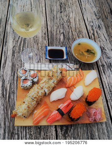 Sushi on wood table. Sushi meal scene featuring a light wood serving tray with nigiri sushi and sushi rolls, miso soup, edamame, soy sauce and wine on a dark wood table