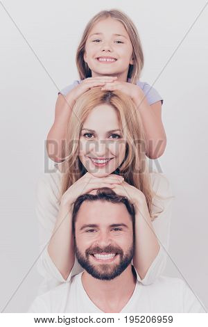 Family photo portrait of three. Parents and small blond daughter are posing on the white background smiling putting each others head on top of each other