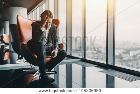 Businessman in formal suit is sitting on orange armchair and holding his head in depression after phone call about his company went bankrupt with copy space for text your logo or advertising message