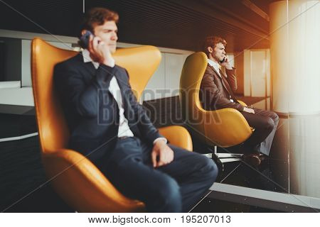 Serious bearded employer talking with his business colleague via smartphone while sitting on curved armchair handsome businessman in formal suite having cell phone conversation in office interior