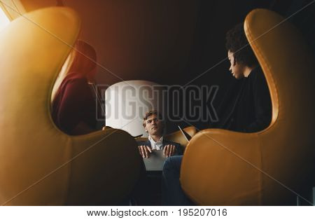 Serious handsome boss entrepreneur during business meeting is attentively listening arguments and information from his female colleagues sitting on yellow curved armchairs and holding laptops