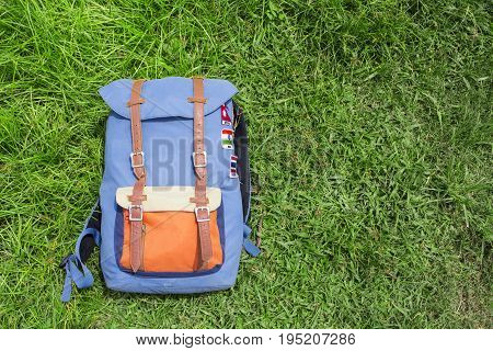 Hipster backpack on summer green grass. Summer travel background photo. Sunny grass lawn with blue backpack. Hipster outdoor banner template with text place. Nomadic lifestyle. Holiday in countryside