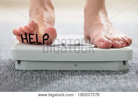 Help Written On Woman's Foot Standing On Weighing Scale Over The Carpet