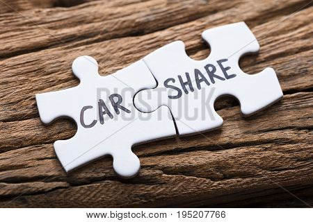 Closeup of connected car share jigsaw pieces on wood