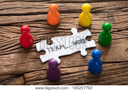 Closeup of teamwork jigsaw pieces surrounded by colorful pawn figurines on wood