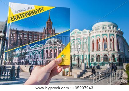 Yekaterinburg, Russia - May 31, 2017: A Woman's Left Hand Holding A Guidebook With Sevastianov's Hou