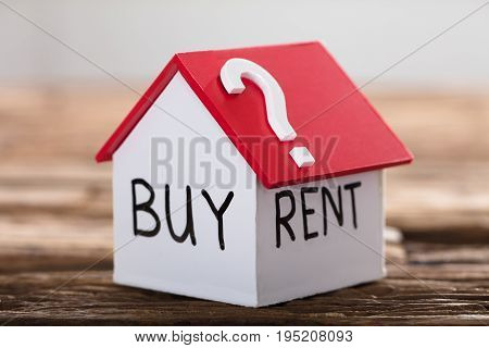 Closeup of buy or rent text with question mark on model house on wood