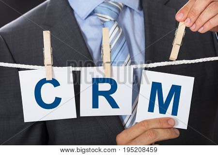 Closeup midsection of businessman pinning CRM papers on clothesline