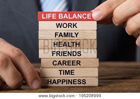 Closeup of businessman building life balance concept with wooden blocks on wood