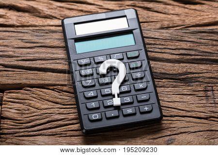 Closeup of question mark and calculator on wooden table