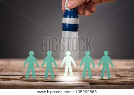 Cropped image of businessman's hand holding flashlight over paper man representing recruitment against gray background