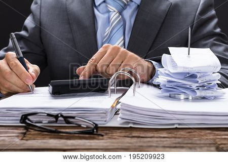 Midsection of businessman calculating invoice with bill stand on documents at table