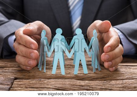 Midsection of businessman covering paper team with hands on wooden table