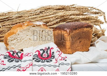 Wheat and rye unleavened bread on the background of a bunch of ears of wheat