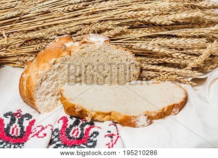 Wheat unleavened bread on the background of a bunch of ears of wheat