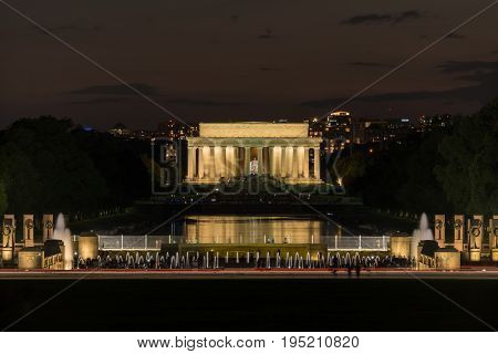 World War 2 memorial and fountains at night with floodlit Lincoln Memorial in background in Washington DC