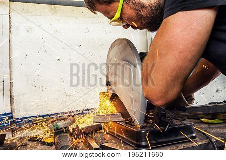 Man Welder Cuts A Metal With A Circular Saw