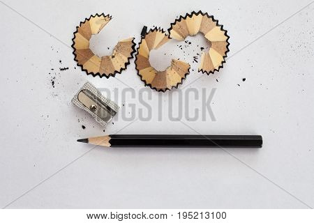 black wooden pencil sharpener and pencil shavings on white paper