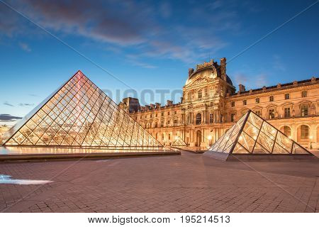 Louvre Museum And The Pyramid At Twilight In Paris, France