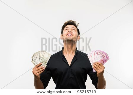 Happy Indian young man holding  new indian currency or 2000 or 500 rupee notes fan, isolated over white background