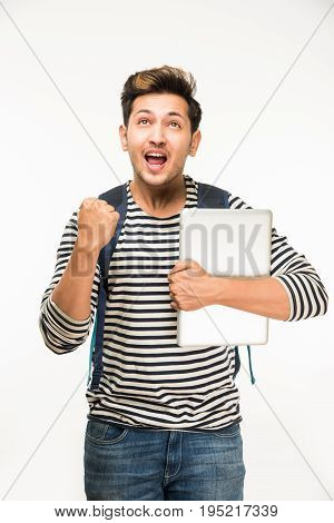 Handsome and young indian Male college student carrying bag on white background while holding college books, laptop or smart phone