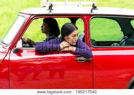 Two travel woman in car road trip waving out the window smiling