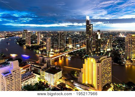 Aerial night view over Bangkok modern office building in bangkok business zone near the river with sunset sky in Bangkok Thailand