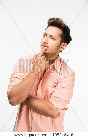 Portrait of a good looking confused Indian Man or handsome Indian man in thinking pose, standing isolated over white background