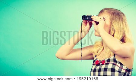 Blonde Woman Looking Through Binoculars Into Distance