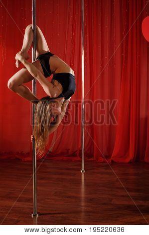 Pole sexy dancer dances on a pylon. She hangs on pylon upside down. Flexibility plasticity and strength.