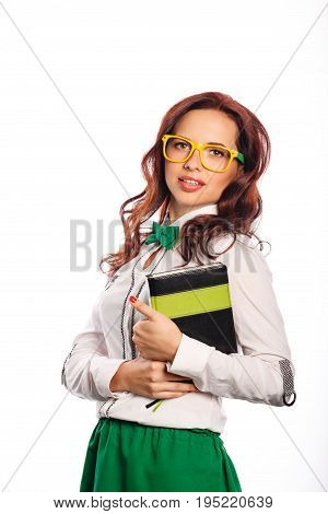 A young attractive girl in a blouse a bow tie and glasses is holding a notebook. Business woman with a diary. Planning of affairs.