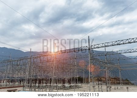 high voltage power transformer substation in valley against cloudy sky