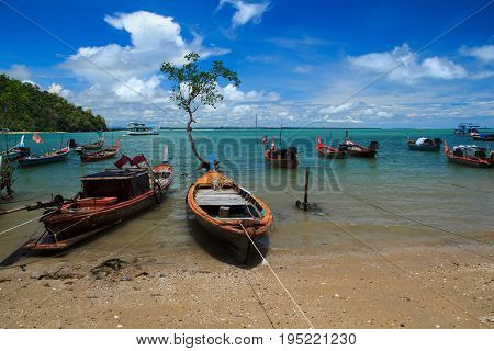 Longtail boat parked shallow due to sea water decreased.