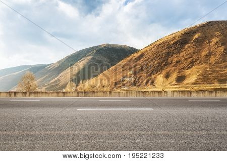 empty asphalt road with the autumn sunshines background. tibet words on the mountain mean :six syllable mantra about tibetan area buddhism useful expressions.