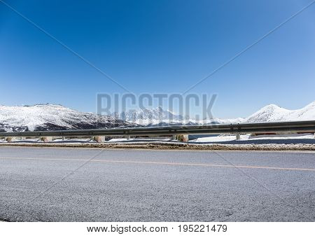 empty asphalt road with snow mountain in tibet plateau the background is namcha barwa peak