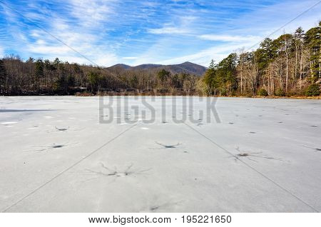 Frozen wintry landscape of cracked ice full of holes at Lake Powhatan in North Carolina