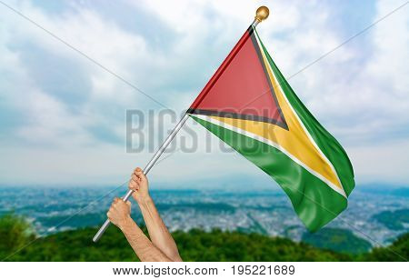 Young man's hands proudly waving the Guyana national flag in the sky, part 3D rendering