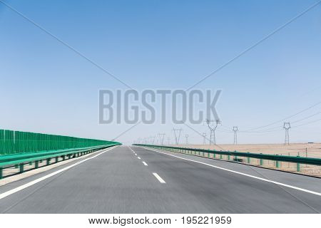 highway on gobi desert road motion blur with power transmission tower on wilderness background
