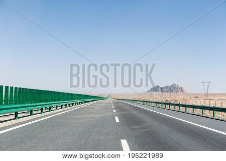 long highway on gobi desert road has been sand blowing with wilderness background